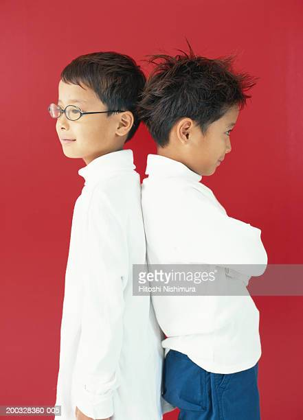 Boys (4-7) standing back to back, side view