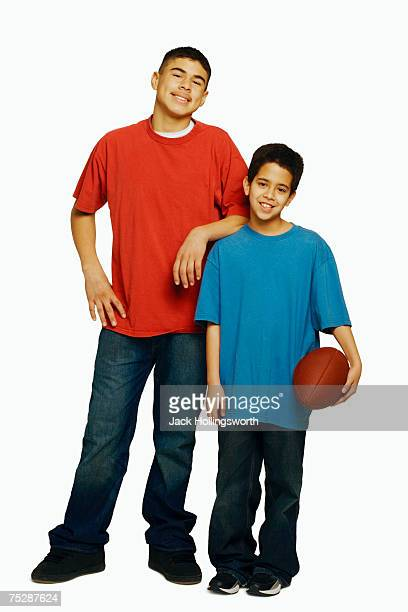 Boys (11-14) standing, holding rugby ball, portrait