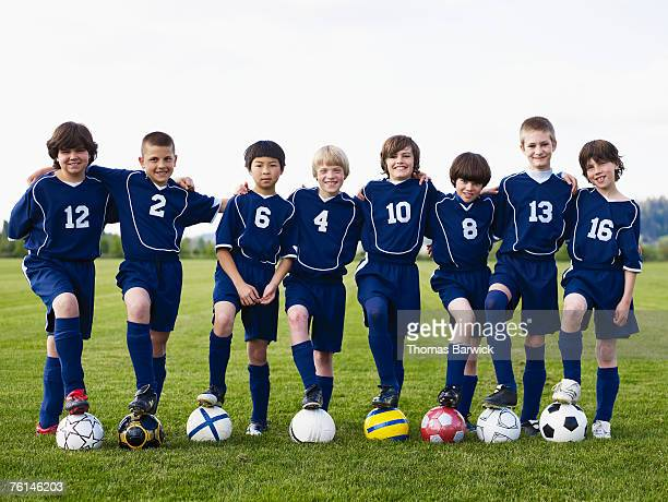 Boys (10-11, 12-13) standing in row on footballs on pitch