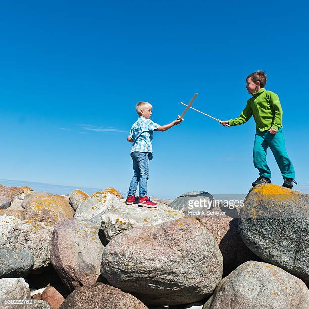 boys standing on rocks and fighting with wooden swords - sword in the stone stock photos and pictures