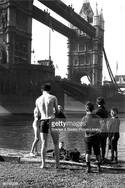 Boys standing on the bank of the River Thames beside Tower Bridge One is drying himself after a swim