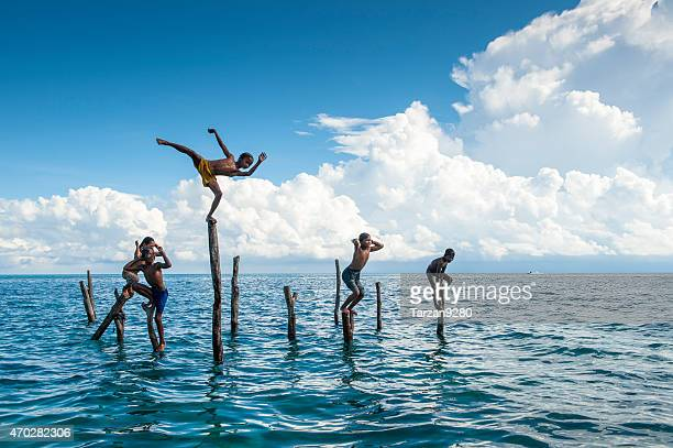 boys standing on the pole, malyasia - sabah state stock pictures, royalty-free photos & images