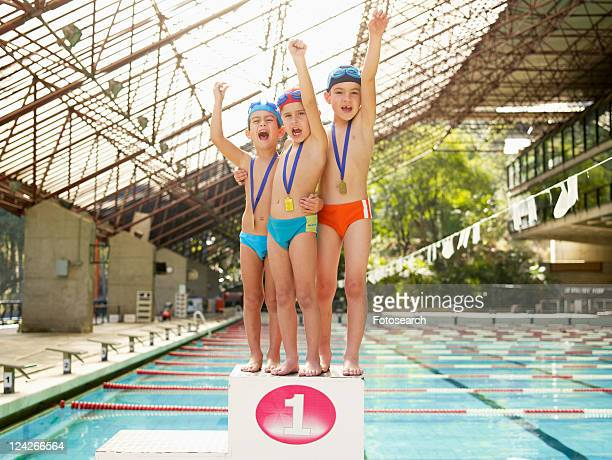 Boys standing on winners podium by swimming pool (portrait)