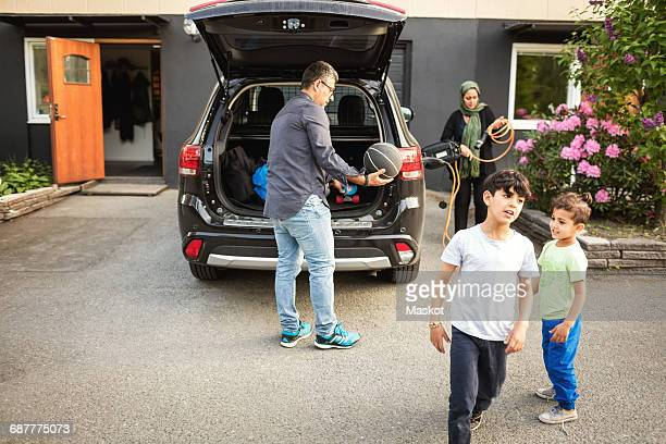 Boys standing while father and mother standing by car outside house