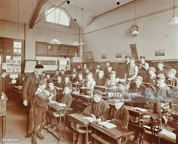 Boys strapping on phylacteries Jews' Free School Stepney London 1908 A class of boys wearing caps sit at their desks with phylacteries The Jews' Free...