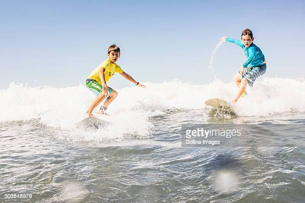 Boys surfing in ocean