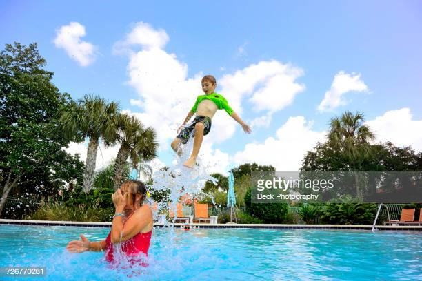boys swimming and splashing - orlando florida stock photos and pictures