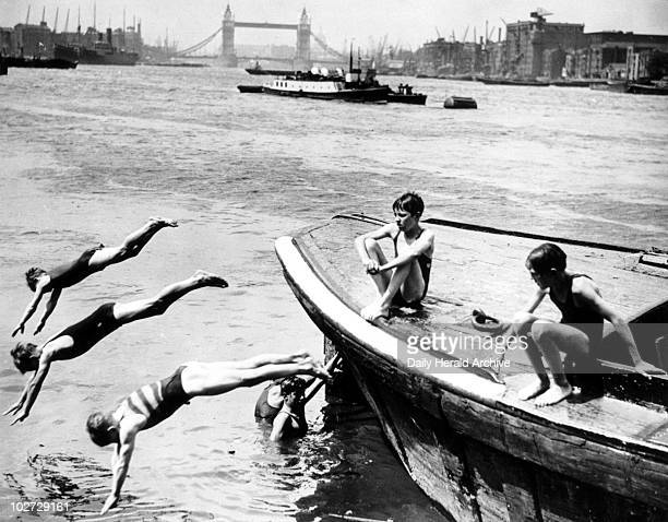 Boys swimming in the River Thames at Rotherhithe London 26 July 1934 'The holidays begin Schoolboys diving and swimming in the River Thames at...