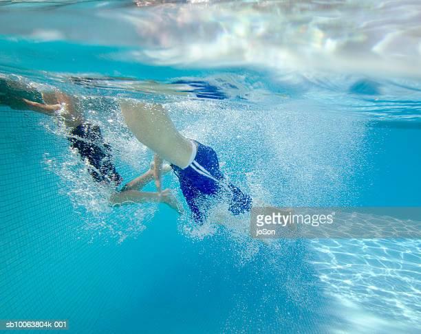 Boys (8-15) swimming underwater in pool
