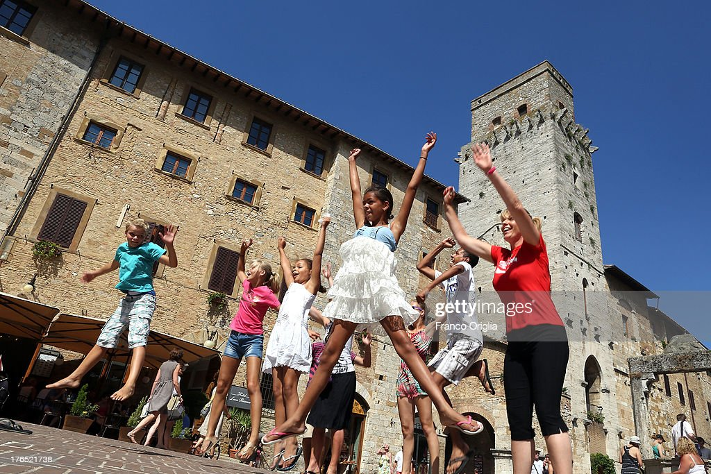Boys take a picture in the central square of San Gimignano on August 14, 2013 in San Gimignano, Italy. San Gimignano is a small walled medieval hill town in the province of Siena, Tuscany. Known as the Town of Fine Towers, San Gimignano is famous for its medieval architecture, unique in the preservation of about a dozen of its tower houses.