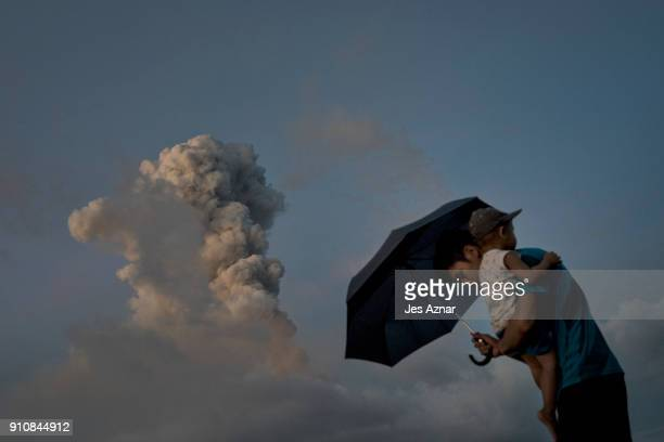 Boys take cover with an umbrela as Mayon spews ash and lava on January 26 in Albay Philippines Over 70000 villagers have been evacuated and camped in...
