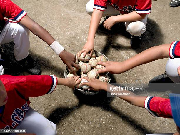 boys (8-10) taking baseballs out of bucket, elevated view - baseball strip stock pictures, royalty-free photos & images