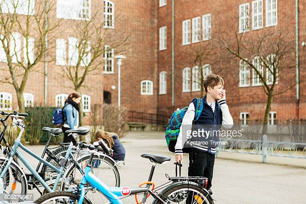 Boys talking on mobile phone by bicycle parking area outside school building