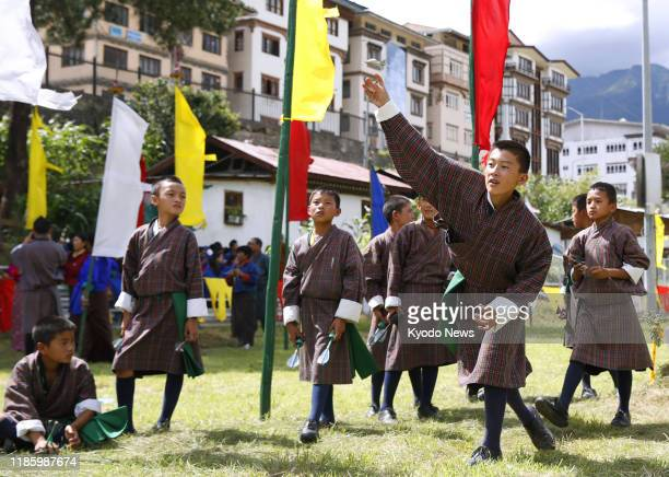 """Boys throw darts at a target 10 meters away as they practice the traditional Bhutanese sport of """"khuru"""" in the capital Thimphu on Aug. 19, 2019."""