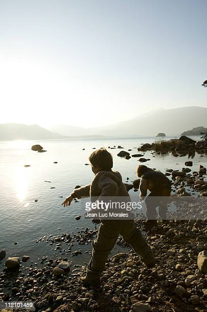 Boys throwing stones in lake