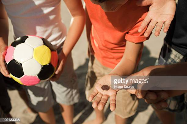 boys tossing a coin - flipping a coin stock pictures, royalty-free photos & images