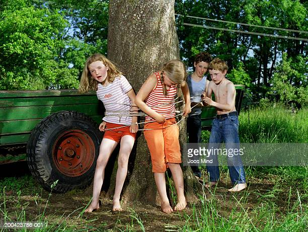Boys (8-10) tying girls (7-9) to tree, outdoors