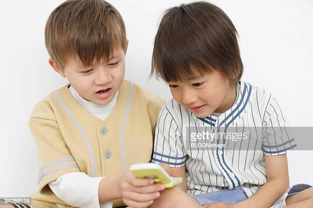 Boys using cellular phone, studio shot
