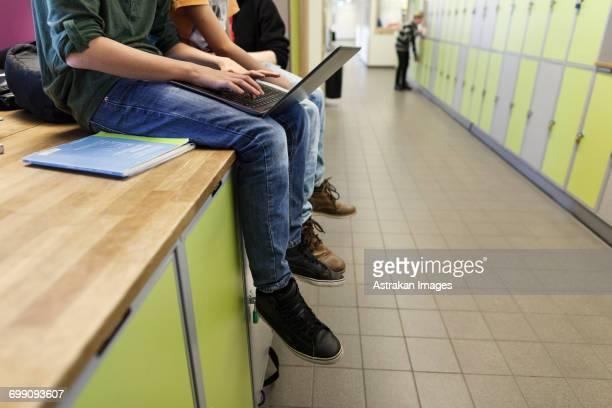 Boys (12-13) using laptop and sitting on lockers in school corridor