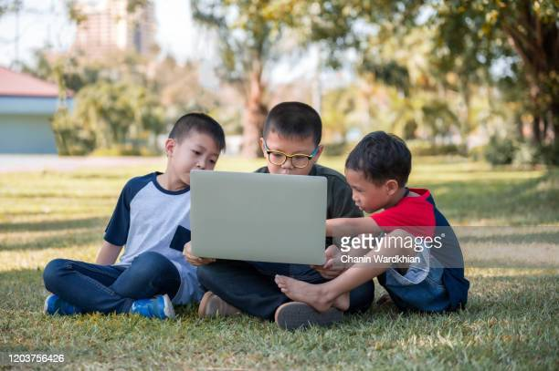 boys using laptop at park - small group of people stock pictures, royalty-free photos & images