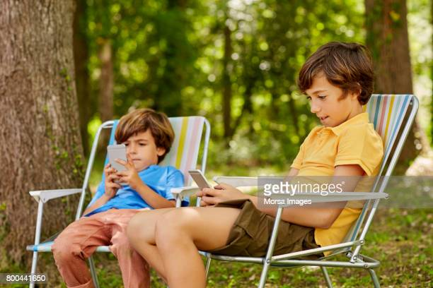 Boys using phones while sitting on deck chairs