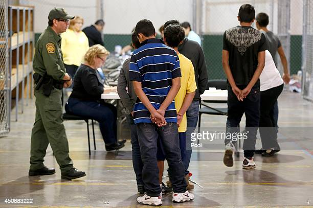 Boys wait in line to make a phone call as they are joined by hundreds of mostly Central American immigrant children that are being processed and held...