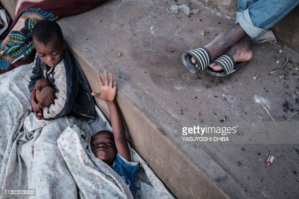 Boys wake up in the morning as they stay in shelter at the stands of Ring ground in Buzi Mozambique on March 23 2019 The death toll in Mozambique on...