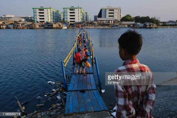 Boys walk across a makeshift bridge to reach their neighbourhood which lies below sea level in Jakarta, Indonesia. Jakarta, one of the world's most...