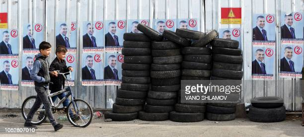 Boys walk past election posters ahead of October 28 presidential elections in Tbilisi on October 23 2018