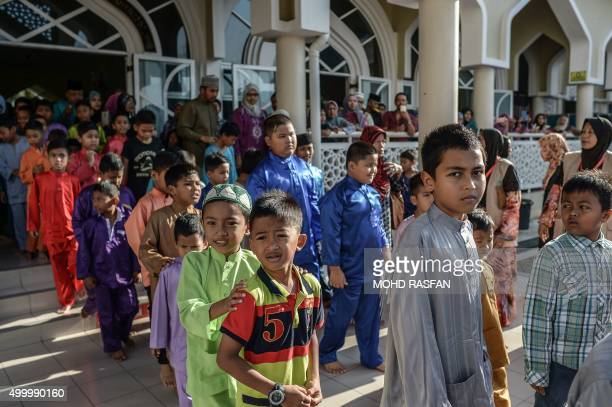 Boys walk together before being hosed down with water during a mass circumcision ceremony at a mosque in Ampang in the suburbs of Kuala Lumpur on...