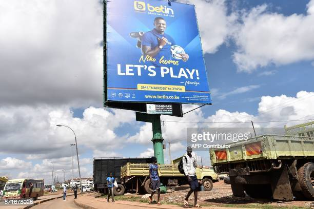 Boys walk under a billboard advertising a popular sports betting site in Nairobi's Kawangware suburb on November 8 2017 The popularity of football...