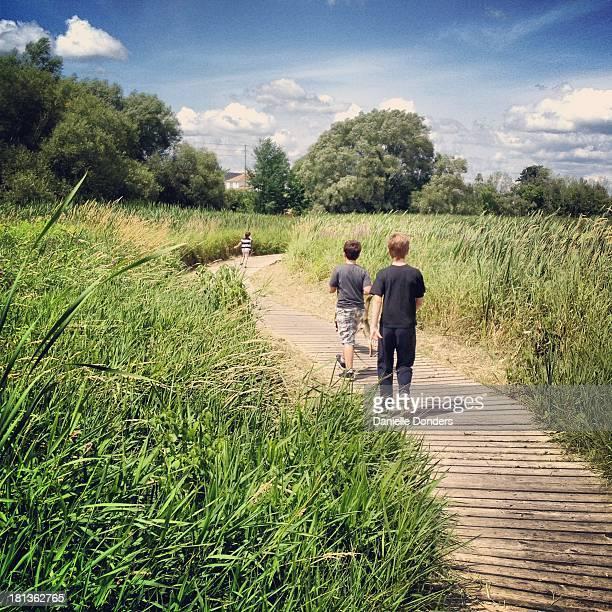 Boys walking on the boardwalk through the reeds