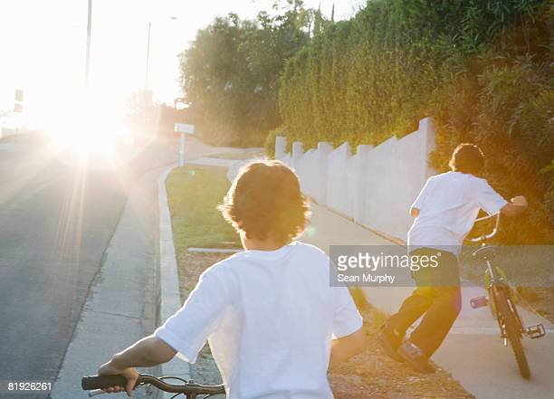 boys walking their bicycles uphill at dusk