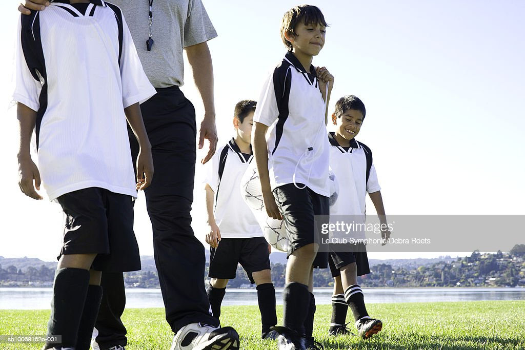 Boys walking with soccer coach on field, : Stockfoto