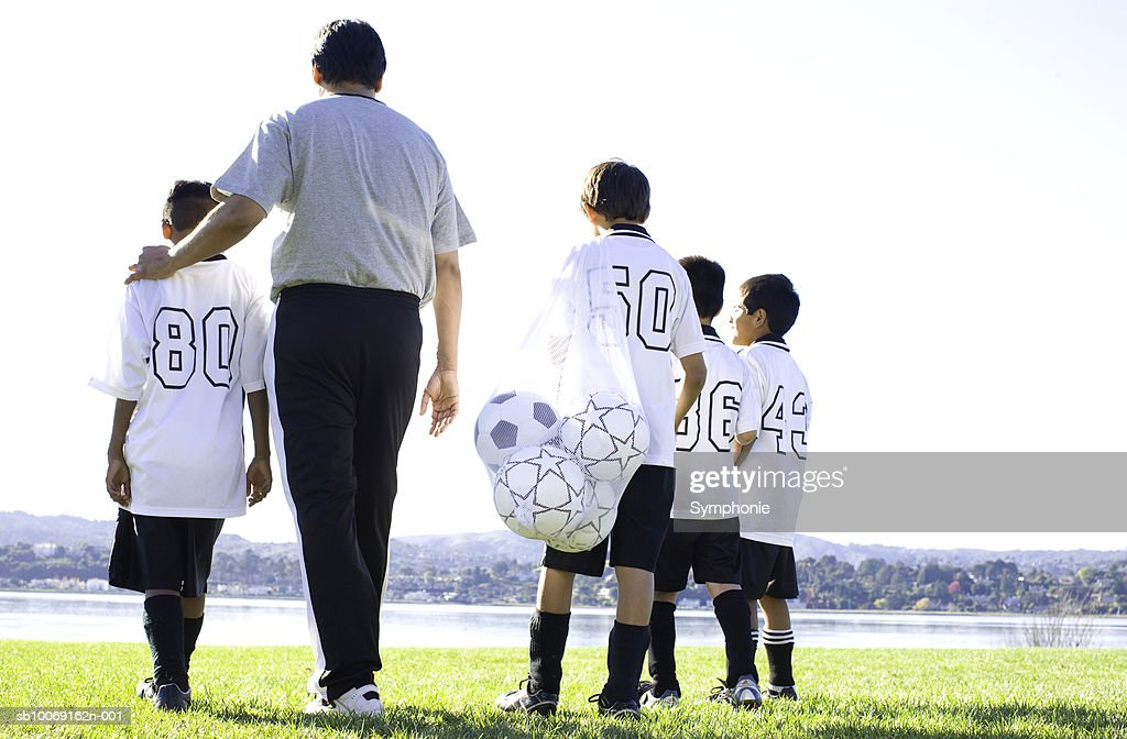 Boys walking with soccer coach on field, rear view : Stockfoto