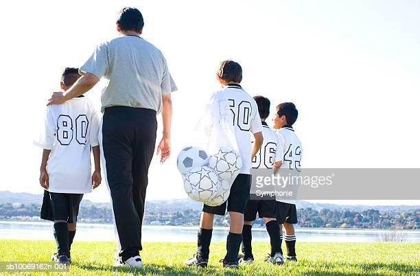 Boys walking with soccer coach on field, rear view
