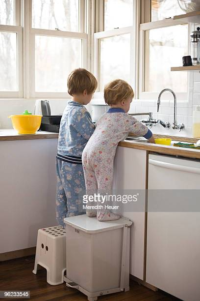 boys wash dishes in the sink