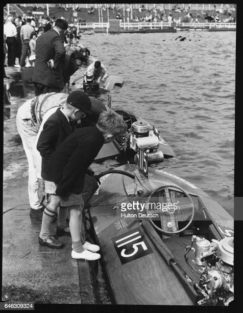 Boys watch as a boat racer prepares his hydroplane for a race