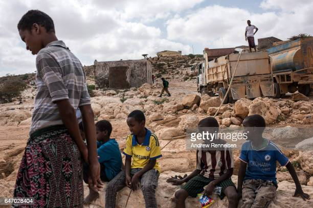 Boys watch as water is pumped from a nearly dried up riverbed on February 24 2017 in Dhudo Somalia People travel up to 75 kilometers to get water as...