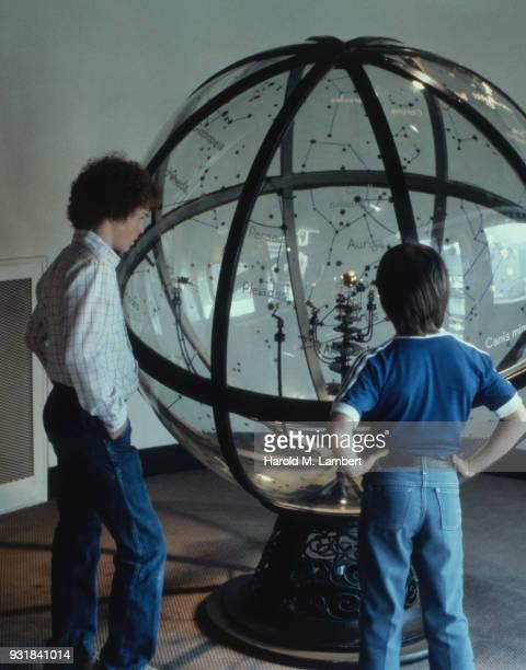 Boys watching constellations in planetarium