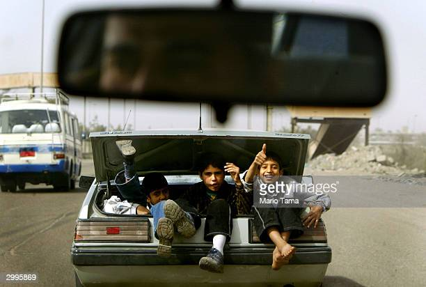 Boys wave as they ride in the trunk of a car February 19 2004 in Baghdad Iraq US administrator Paul Bremer said today changes are possible in the new...