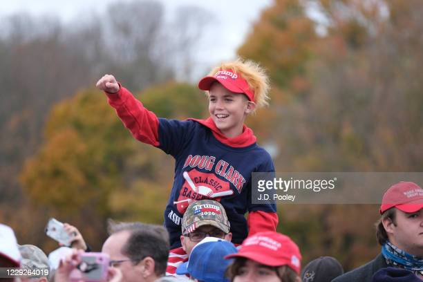 Boys waves ahead of U.S. President Donald Trump speaking to supporters during a campaign event on October 24, 2020 in Circleville, Ohio. President...