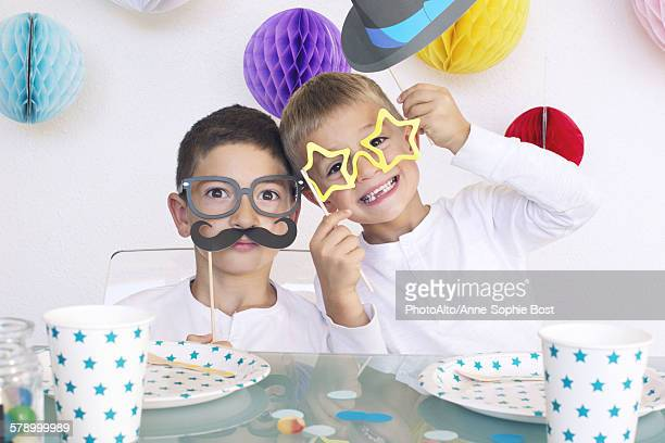 Boys wearing funny disguises at birthday party
