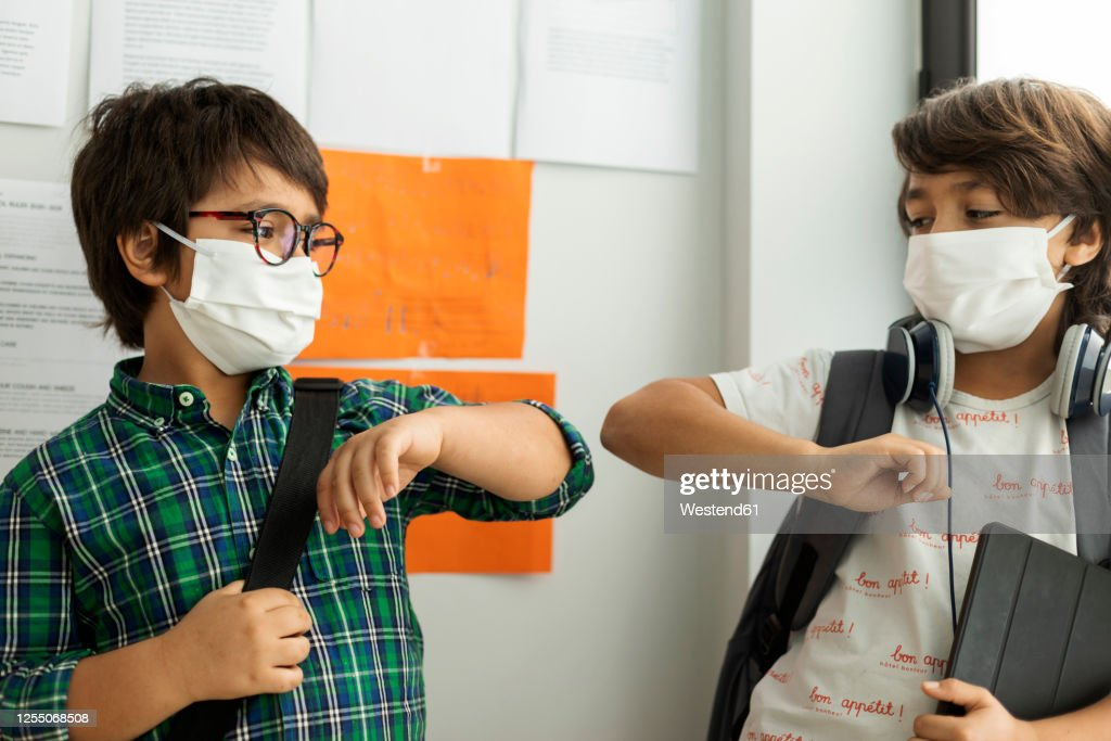 Boys wearing masks giving elbow bump while standing against wall in school : Stock-Foto