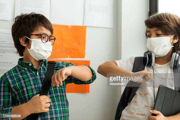 boys wearing masks giving elbow bump while standing against wall in school - riapertura delle scuole foto e immagini stock