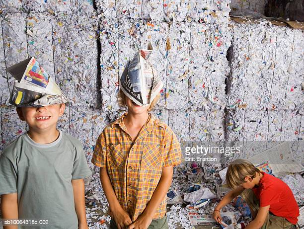 boys (6-7) wearing paper hat, another boy (8-9) making paper aeroplane in recycling centre - セーラーハット ストックフォトと画像