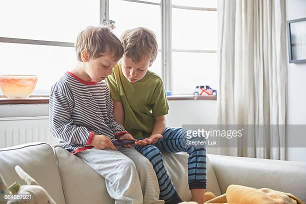 Boys wearing pyjamas sitting on sofa looking at smartphone