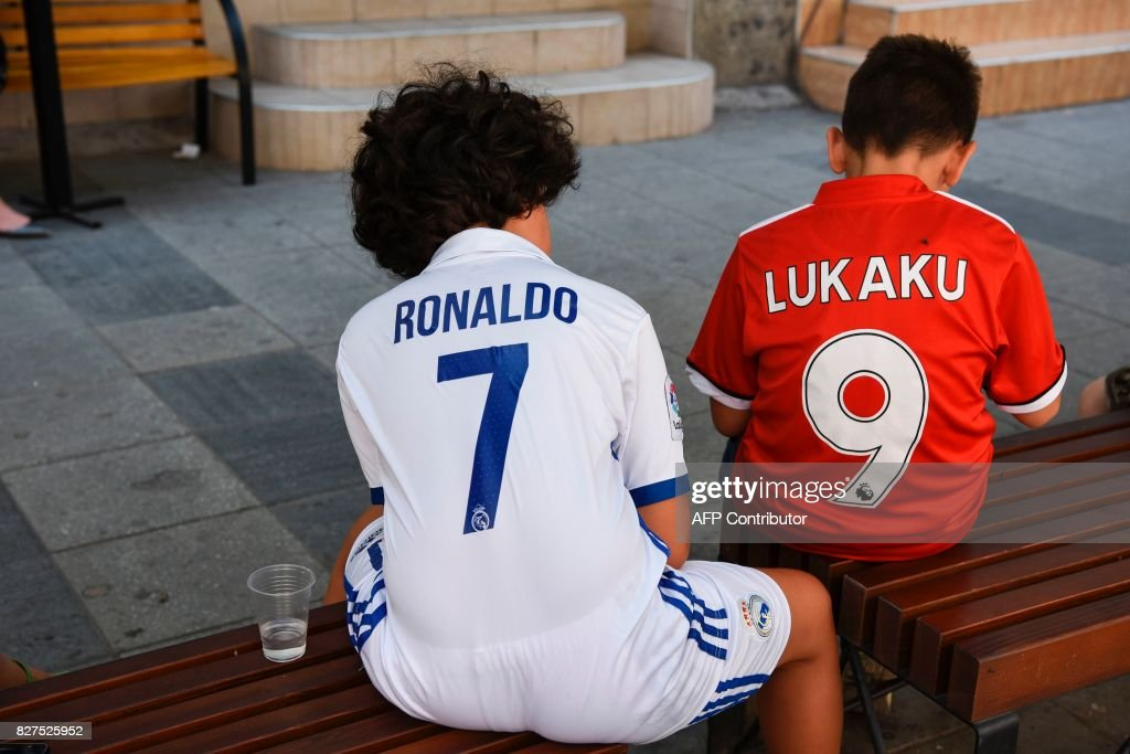 Boys wearing Real Madrid's and Manchester United jerseys sit on a bench in Skopje on August 8, 2017 ahead of the UEFA Super Cup football match between Real Madrid and Manchester United. / AFP PHOTO / Armend NIMANI