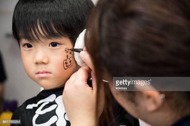 ハロウィーンの日に塗られて得る男の子。