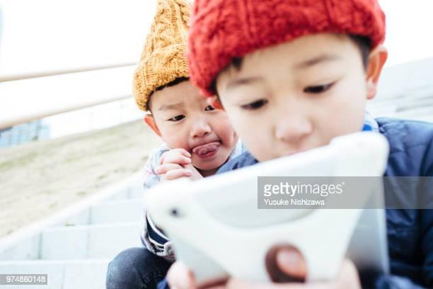 boys who operates a tablet - yusuke nishizawa stock-fotos und bilder